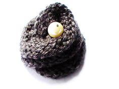 Broche gris anthracite en 51 % laine peignée et 49 % acrylique en forme de fleur avec une perle ivoire nacrée. Elle fait 7,5 cm de diamètre et 4 cm d'épaisseur, la perle est de 1,2 cm de diamètre. Elle peut être accrocher à un manche du vêtement au col d'un écharpe, un sac, un manteau etc. Elle est très jolie et chic!