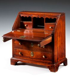18th Century Miniature Fruitwood Bureau    18th Century fruitwood bureau, the top above a fall enclosing a fitted interior with two drawers and pigeon holes, the shaped arches being secret drawers, above three long graduated drawers fitted with brass escutcheons and knob handles, raised on shaped bracket feet.  £ 4,950