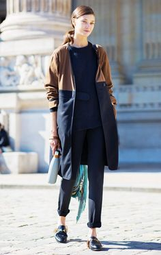 Diana Moldovan wears a sweater, cropped pants, colorblock coat, and backless Gucci loafers