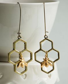 Honeycombs hexagons create the perfect home for a golden honey bee. These nature inspired beehive style earrings hang from simple ear wires. They