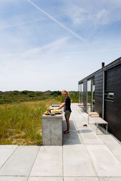 Concrete outdoor kitchen  deck and black wood panel house in Denmark | Contour Arkitekter