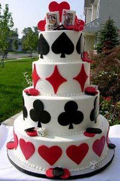 For my Hubby...  A very unique four tier red and white wedding cake decorated with black and red suits from the deck of playing cards. The hearts and diamonds are in red, and the spades and clubs are in black. The wedding cake topper has three red hearts sitting on top with the King & Queen of heart cards and a pair of dice. Embellished with casino red and black gambling chips and white dice