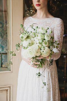 An organic-shaped, all white ranunculus wedding bouquet | Brides.com
