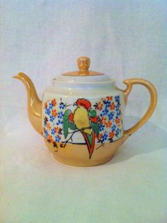 This handpainted lustreware teapot is a perfect size and decorated in an eye catching desgin of a green, yellow and red bird perched on a branch with red and blue flowers in the background.