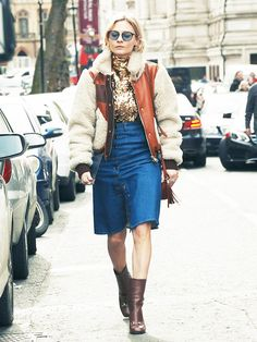 Pandora Sykes wears a shearling bomber jacket, sequin roll neck top, button-front denim skirt, and Gucci boots