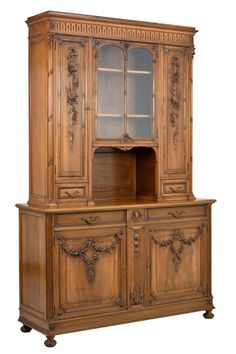 Morton Auctioneers A FRENCH LOUIS XVI STYLE BUFFET A DEUX CORPS   The buffet a deux corps having a stepped cornice over the linenfold carved frieze, above two glazed doors flanked by paneled doors, over the rectangular top and conforming case, fitted with two drawers over two paneled doors, carved with foliate swag decoration, raised on a flared plinth base, ending in squat ball feet.  H 93 1/2 x W 61 1/2 x D 20 1/2 inches.  Estimate $ 600-900