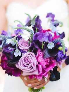 Jewel toned purple wedding bouquet with roses, sweet pea, veronia and calla lilies