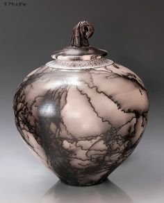 Raku pottery. This look of this piece is created by applying horsehair to the clay just before it is fired. Thus you see the markings of the horsehair that burns during ground fired pottery.