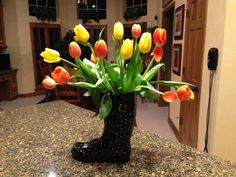 Use a styrofoam cup inside the rainboot as a vase.  Adding ice to the water to keeps the flowers fresh.