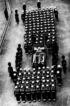 George Rodger  G.B. ENGLAND. London. Winston Churchill's funeral. The gun carriage carrying the body of Winston Churchill is carried slowly through the streets of London towards St. Paul's Cathedral, flanked by a military escort of all ranks and services. 1965