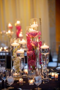tubular vases with flowers and floating candles