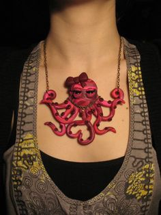 """Pretty-in-Pink Octopus Necklace - OOAK Polymer Clay Jewelry            This cute lil' octopus was hand-sculpted out of pink, shimmering silver, and burgundy polymer clay. It is packed full of details like a bright bow on top of her head, a """"sea glass"""" necklace, and tentacles curled into a heart. She measures approximately 4.5 inches wide by 4 inches tall and is attached to an antique brass chain with a matching lobster clasp and jump ring connector. The necklace measures 19 inches long with…"""