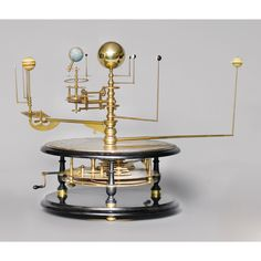 A LIMITED EDITION GRAND ORRERY, GEORGE GYORI, RECENT mounted on a wooden ebonised base, separated by brass and wooden columns, engraved with signs of the zodiac, months of the year and the four seasons, the central column projecting upwards holding six rings each with a projecting arm with mounted globe and planets, brass handle to side of drum which, when turned, moves the projecting arms and therefore the planets and also the movement of the lunarium height 53cm