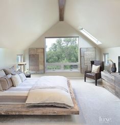 In the master bedroom suite, which occupies the entire upper level, skylights were added to enhance the natural light while allowing the owners to look into the treetops. The platform bed is from Environment Furniture, and the chair is custom by Lee Industries.