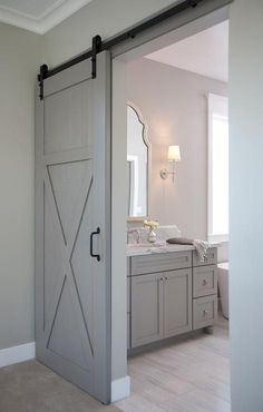Gray walls highlight a gray barn door on black rails leading to an en suit bathroom featuring a gray washstand accented with polished nickel hardware and topped with a white marble countertop fitted with an oval sink and a polished nickel antique hook and spoiut faucet positioned under a white arched mirror lit by a Bryant sconce illuminating wood like tiled floors and light gray bathroom walls. by effie