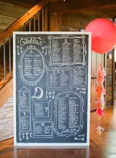 In lieu of escort cards, an oversized chalkboard served as the seating chart. | Photo: Taylor Lord Photography