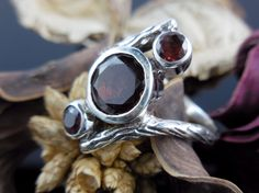 Made with 8mm and 4.5mm round faceted garnet gemstones and textured sterling silver ring. Size 8.75