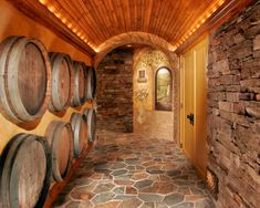 A unique barrel-vaulted ceiling is illuminated by low-voltage accent lighting, concealed by tailored molding. Imported wine casks were cleverly repurposed as part of a decorative wall display.