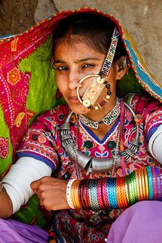 India | Portrait of a woman from the Marwada Meghwal Harijan tribe wearing traditional clothing and a large golden wedding ring through her nose in the village of Bhirendiara, located roughly 50km from Bhuj in the Kutch District. | © Kimberley Coole