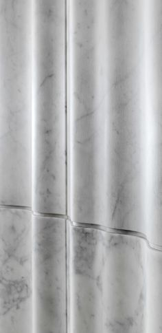 "As gauzy vertical draperies, the ""chiffon"" 3d stone wall tiles give movement and depth to the wall thanks to the variety of their different-sized vertical folds. From the ""Drappi di Pietra"" collection."
