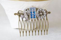 This beautiful handmade Dr. Who-inspired hair comb features a silver-plated blue enamel Tardis Police Box Charm surrounded by a