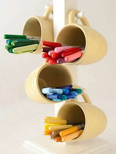 BHG:  Turn a Mug Tree into Storage for Pens And Markers-Many of us have these mug trees in our kitchens, but have you thought about turning it into a kitschy storage unit for scrapbooking supplies? The individual cups allow you to group writing tools by color, and since most manufacturers recommend storing pens and markers horizontally, the angle is just right. It's also easy to take color groups to another room to work. Approximate cost: $30 (with mugs)
