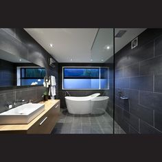 Large-format charcoal tiles in the bathroom replicate the concrete block on the exterior of the house. A freestanding bathtub and cantilevered wood vanity reinforce the sense of simplicity that characterises the rest of the house.