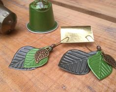 Pair of earrings mounted on a bronze rod. Capsule Nespresso capsule, green, trimmed with a bronze leaf charm. Length: approximately 6 cm cm width) Very light and comfortable to wear. Recycled Jewelry, Unique Jewelry, Cappuccino Machine, Dyi Crafts, Coffee Pods, Bijoux Diy, Jewelry Crafts, Jewelry Making, Handmade Gifts