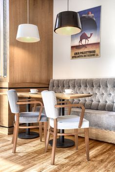 This Polish cafe has lots of comfortable upholstered banquettes, chairs and sofas. Vintage art posters add some color to the white walls.