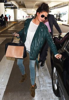 Chrissy Teigen's chic travel style: oversized green leather motorcycle jacket and brown suede boots