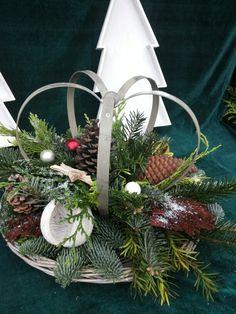 Kerststuk met zinken kroon op een ratan dienblad