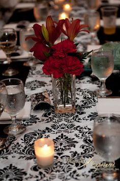 Table decor. Red flowers to accent black and white damask theme.  Image by TimelessExposuresPhotography.com