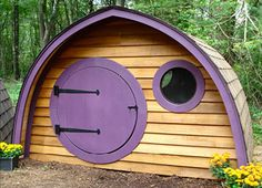 Hobbit Hole Playhouse with round front door and windows, all natural wood construction, purple trim on Etsy, $2,795.00