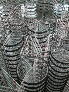 "Ai Weiwei, Forever Bicycles installation (2 of 2). ""Using the sheer size, number and fluctuating movements of the piece, the artist intends to represent his home country of China where bicycles are the common element in transportation and also the ever changing population & landscape"" & invites viewer to walk or crawling through the installation. Caption at ink"