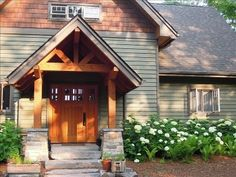 Front entrance with Timber Frame porch surrounded by white hydrangeas