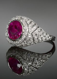 "A radiant Burma ruby commands attention at the center of this dazzling ring. Set amid a host of diamonds in a stunning pierced dome platinum setting, this 2.80-carat cushion cut gem glimmers with the rare ""pigeon's blood"" coloring for which Burma rubies are coveted. The ruby is certified by the AGL for color."