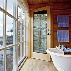 A Bath with a View-floor to ceiling windows, on one wall, let in plenty of light to a clawfoot porcelain tub while teak wood paneling lines the walls of the bathroom