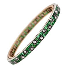 Edwardian Emerald Diamond Gold Platinum Bangle Bracelet | From a unique collection of vintage bangles at https://www.1stdibs.com/jewelry/bracelets/bangles/