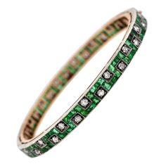 Edwardian Emerald Diamond Gold Platinum Bangle Bracelet | From a unique collection of vintage bangles at https://www.1stdibs.com/jewelry/bracelets/bangles/