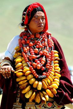 Nomadic Tibetan traditionally store their wealth in jewelry and ornaments, easily transported and handed down from generation to generation. Ornaments and stones have deep religious and cultural significance. Gold, silver, coral, turquoise, ancient dzi bead necklaces, amber necklaces and large Ghau amulets made of gold and silver are worn. |