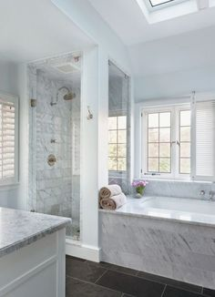 Dark slate floors and Carrara marble make this contemporary bathroom a soothing escape...