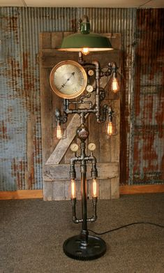 """This design is made to order and may take up to 3 weeks to ship. We sold and shiped this lamp June 2017.  Price includes 12"""" rare antique steam gauge Four 2"""" steam gauges Antique gear from an old tractor (base) We will build a similar version and supply photos for final approval before we ship Antique service station green shade Antique water meter Shipping included (usa) Stands about 70"""" t"""