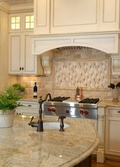 Dreamy kitchen with sand colored countertops and tumbled marble backsplash.