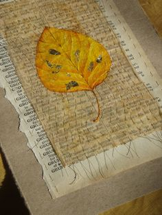 Acrylic painting of an ornamental pear leaf on tea bag paper, with metal (gold) leaf, hand sewn to an old dictionary page.
