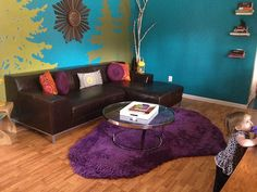 Eve's lovely turquoise wall -- with  green tree stencils! -- dark couch and purple shaggy rug.