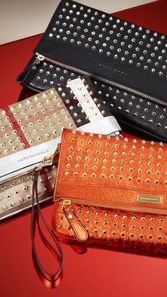 A selection of studded foldover crossbody bags with directional stud detail in classic black, oversize check and vibrant metallic tangerine for S/S13
