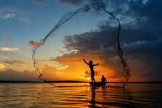 Silluate fisherman nets,Thailand - Silluate fisherman trow the nets on the boat in during sunset,Thailand