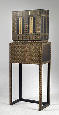 Representative of classicalvintageViennese design from the Jugenstil is the cabinet on stand above exhibited at the Vienna Kunstschau in 1909. The wood frame is covered in black buckskin and embossed in gold and geometric patterns. This is a very luxurious piece of furniture. It looks like the type of piece Gustav Klimt would have used as the backdrop in one of his fabulous paintings. While clearly of the period, it would look perfect in a contemporary home amongst modern furnishings. The…