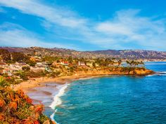 Rocky cliffs with palm trees fill the leftside foreground leading back to beach and breaking surf of Laguna Beach, California.