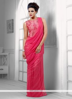 Magnificent pink net wedding gown featuring stick on crystals and resham embroidered decorative patterns on the upper torso and plain lower torso. Greek goddess inspired draping style pleats on one si...